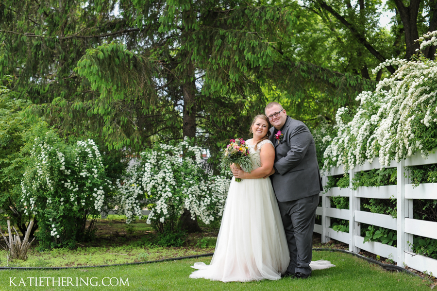 Bride & Groom posed near Bridal Wreath Spirea